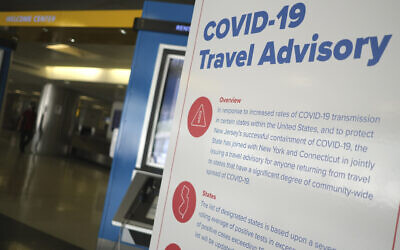 Illustrative: A sign warns airline passengers about a COVID-19 travel advisory at Newark Liberty International Airport in Newark, New Jersey, July 1, 2020. (Seth Wenig/AP)