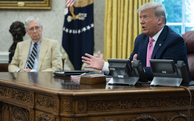 Senate Majority Leader Mitch McConnell of Ky., listens as US President Donald Trump speaks during a meeting in the Oval Office of the White House, Monday, July 20, 2020, in Washington. (AP Photo/Evan Vucci)
