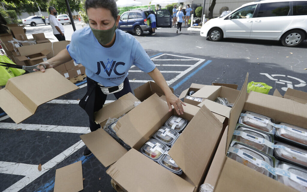 Illustrative: Volunteer Malka Rodrig unpacks meals at a kosher food drive-thru distribution site, July 29, 2020, at the Greater Miami Jewish Federation building in Miami. (AP Photo/Wilfredo Lee)