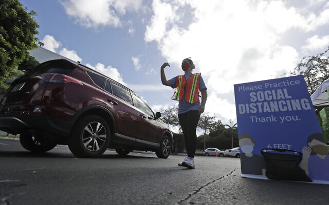 Illustrative: Shayna Weiss directs drivers at a kosher food drive-thru distribution site, July 29, 2020, at the Greater Miami Jewish Federation building in Miami. (AP Photo/Wilfredo Lee)