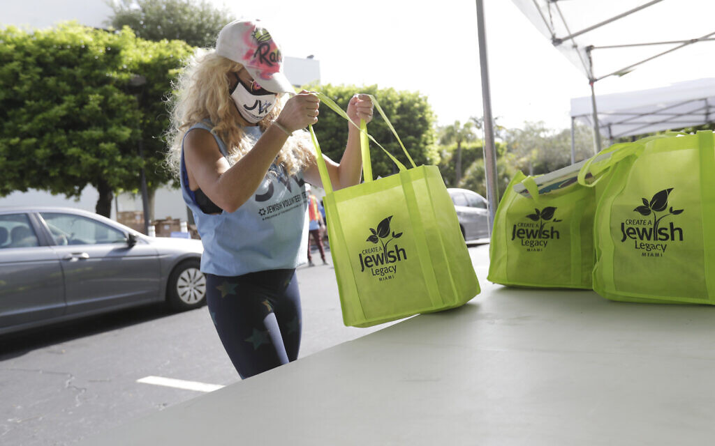 Illustrative: Volunteer Rachel Friedland prepares to load food in a car at a kosher food drive-thru distribution site, July 29, 2020, at the Greater Miami Jewish Federation building in Miami. (AP Photo/Wilfredo Lee)