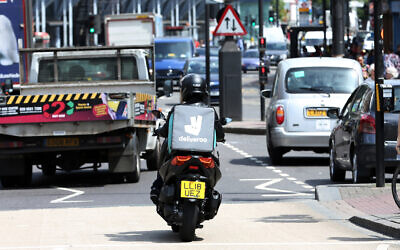 Illustrative: A Deliveroo driver is seen in traffic in north London, June 15, 2018. (AP Photo/Robert Stevens, File)
