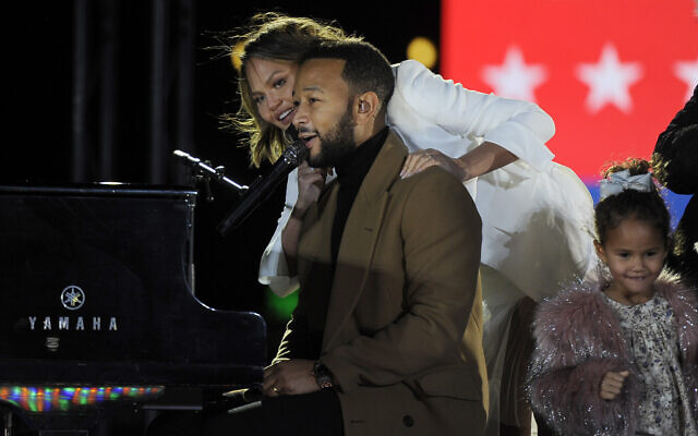 """Performer John Legend, his wife Chrissy Teigen and their daughter Luna greet a crowd gathered during a drive-in """"get out the vote"""" rally featuring Democratic vice presidential candidate Kamala Harris, Nov. 2, 2020, in Philadelphia. (AP Photo/Michael Perez)"""