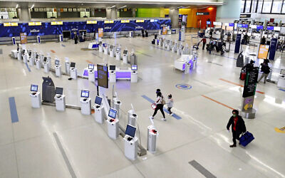 Travelers walk through the nearly empty JetBlue terminal at Logan Airport, Friday Nov. 20, 2020, in Boston. (AP Photo/Michael Dwyer)
