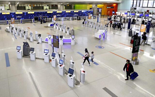 Travelers walk through the nearly empty JetBlue terminal at Logan Airport, Friday Nov. 20, 2020, in Boston. (AP Photo/Michael Dwyer)