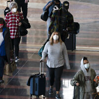 Travelers wearing masks walk to and from their planes at Ronald Reagan Washington National Airport, Nov. 24, 2020, in Arlington, Virginia (AP Photo/Jacquelyn Martin)