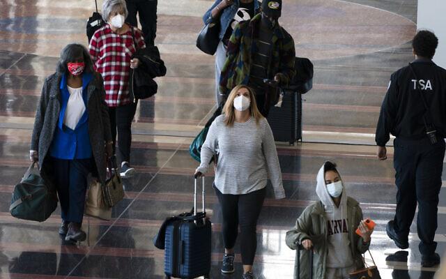 Travelers wearing masks walk to and from their planes at Ronald Reagan Washington National Airport, Nov. 24, 2020, in Arlington, Virginia (AP Photo/Jacquelyn Martin)