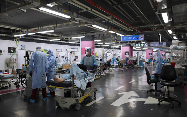 Medical personnel wearing protective equipment treat COVID-19 patients in an intensive care ward that has been converted from underground parking, at Rambam Hospital in the northern city of Haifa, December 15, 2020 (AP Photo/Oded Balilty)