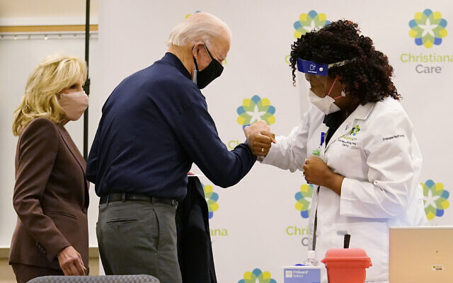 President-elect Joe Biden fist bumps with nurse practitioner Tabe Mase after receiving his first dose of the coronavirus vaccine at ChristianaCare Christiana Hospital in Newark, Del., Monday, Dec. 21, 2020, as Jill Biden looks on. (AP Photo/Carolyn Kaster)