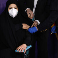 Tayebeh Mokhber is injected with the Coviran coronavirus vaccine produced by Shifa Pharmed, part of a state-owned pharmaceutical conglomerate, in a ceremony in Tehran, Iran on Dec. 29, 2020. (AP/Aref Taherkenareh)