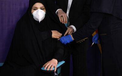Tayebeh Mokhber is injected with the Coviran coronavirus vaccine produced by Shifa Pharmed, part of a state-owned pharmaceutical conglomerate, in a ceremony in Tehran, Iran on December 29, 2020. (AP/Aref Taherkenareh)