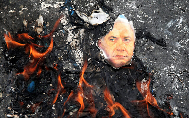 A portrait of Benjamin Netanyahu is set on fire during an annual pro-Palestinian rally in Tehran, Iran, Friday, July 10, 2015. (AP/Ebrahim Noroozi)