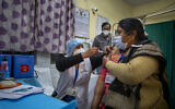 A health worker engages in a COVID-19 vaccine delivery system trial in New Delhi, India, Jan. 2, 2021 (AP Photo/Altaf Qadri)