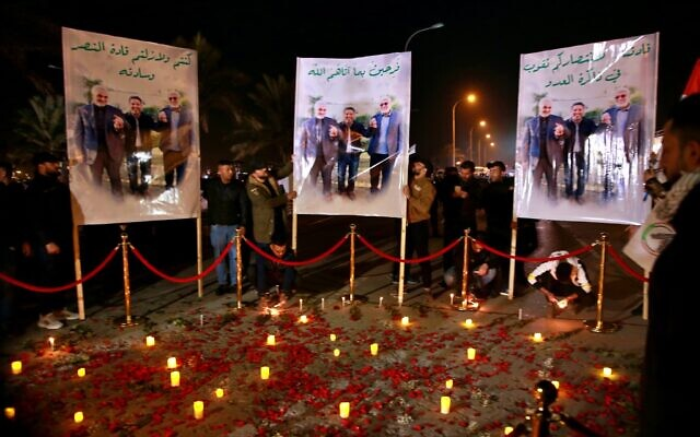 Popular Mobilization Forces and their supporters light candles at Baghdad's international airport on the first anniversary of the killing of Abu Mahdi al-Muhandis, deputy commander of the PMF and Gen. Qassem Soleimani, head of Iran's Quds forces, on Saturday, January 2, 2021. (Khalid Mohammed/AP)