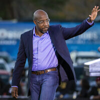 Democratic US Senate candidate Rev. Raphael Warnock waves to supporters during a drive-in rally, Jan. 3, 2021, in Savannah, Georgia (AP Photo/Stephen B. Morton)