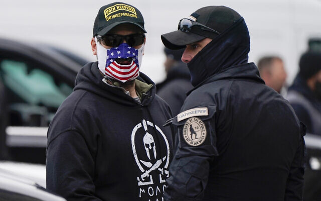People wearing hats and patches indicating they are part of Oath Keepers attend a rally at Freedom Plaza January 5, 2021, in Washington, in support of US President Donald Trump. (AP Photo/Jacquelyn Martin)