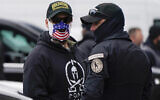 People wearing hats and patches indicating they are part of Oath Keepers attend a rally at Freedom Plaza Tuesday, Jan. 5, 2021, in Washington, in support of President Donald Trump. (AP Photo/Jacquelyn Martin)