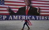 A woman draped in an American flag walks past a banner supporting US President Donald Trump during a rally on Jan. 6, 2021, in Huntington Beach, Calif. (AP/Jae C. Hong)