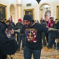 Trump supporters gesture to US Capitol Police in the hallway outside of the Senate chamber at the Capitol in Washington, January 6, 2021. (AP Photo/Manuel Balce Ceneta)