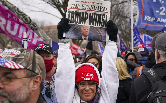 A supporter of President Donald Trump holds up a newspaper with a false headline, Wednesday, Jan. 6, 2021 in Washington, shortly before the assault on the US Capitol (AP Photo/John Minchillo)