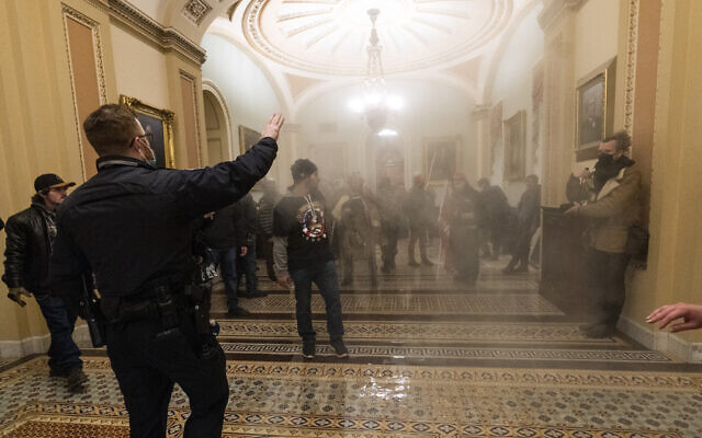 Smoke fills the walkway outside the Senate Chamber as supporters of US President Donald Trump are confronted by US Capitol Police officers inside the Capitol, January 6, 2021 in Washington.  (AP Photo/Manuel Balce Ceneta)