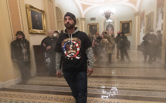 Smoke fills the walkway outside the Senate Chamber as supporters of US President Donald Trump are confronted by US Capitol Police officers inside the Capitol, in Washington January 6, 2021. (Manuel Balce Ceneta/AP)