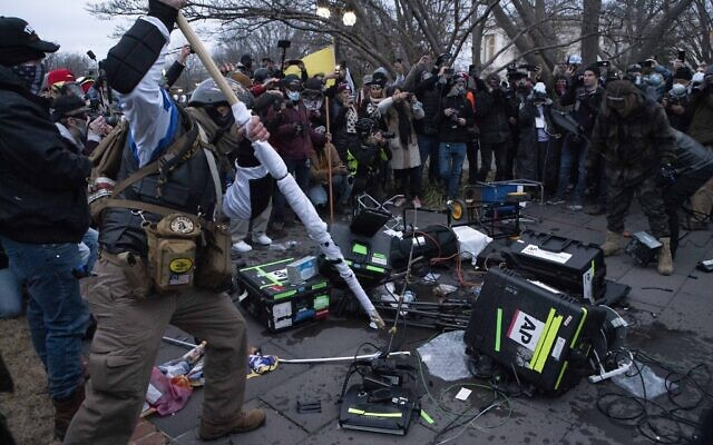 Demonstrators break TV equipment outside the the US Capitol on Wednesday, Jan. 6, 2021, in Washington.  (AP/Jose Luis Magana)