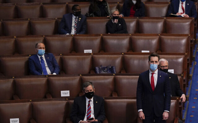Sen. Josh Hawley rises to join House Republican members to object to confirming the Electoral College votes from Pennsylvania during a joint session of the House and Senate to confirm the Electoral College votes cast in November's election, at the Capitol, Jan 7, 2021, in Washington. (AP Photo/Andrew Harnik)