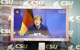 German Chancellor Angela Merkel  seen on a screen as she makes a statement on the events in Washington with the storming of the Capitol building by supporters of US President Donald Trump supporters at the beginning of the digital press conference at the winter retreat of the CSU parliamentary group in the Bundestag, Berlin, Germany, January 7, 2021. (Kay Nietfeld/Pool via AP)