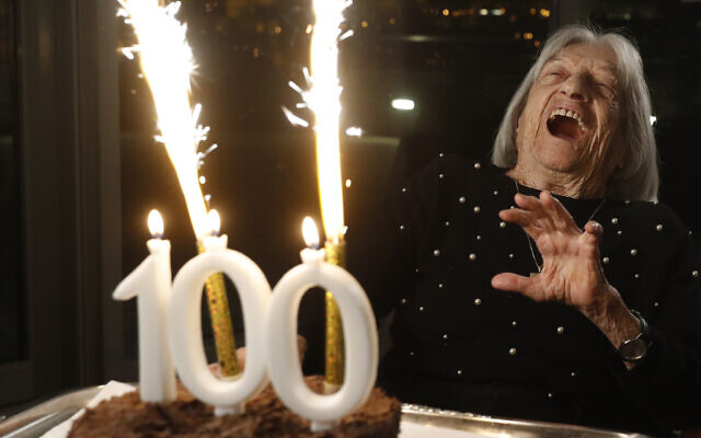 Agnes Keleti, former Olympic gold medal winning gymnast, reacts to fireworks going off on her birthday cake in Budapest, Hungary, Jan. 4, 2021 (AP Photo/Laszlo Balogh)