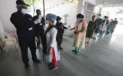 Health workers check the body temperature of volunteers participating in a trial run of a COVID-19 vaccine delivery system in Ahmedabad, India, January 8, 2021. (AP Photo/Ajit Solanki)