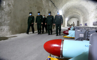In this photo released Jan. 8, 2021, by Sepahnews, the website of the Iranian Revolutionary Guard, commanders of Iran's paramilitary Revolutionary Guard walk past missiles during a visit to a new military base in an undisclosed location in Persian Gulf in Iran. (Sepahnews via AP)