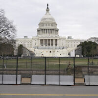 A woman walks past security fencing protecting the West Front of the US Capitol in Washington, January 8, 2021, as preparations take place for President-elect Joe Biden's inauguration after Trump supporters stormed the building. (AP Photo/Patrick Semansky)