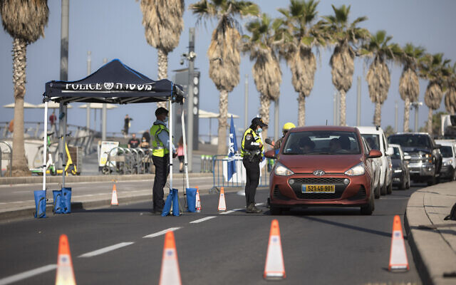 Police officers check cars at a checkpoint during a nationwide lockdown to curb the spread of the coronavirus, in Tel Aviv, January 10, 2021. (AP/Sebastian Scheiner)