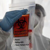 An Israeli health care professional holds a COVID-19 test sample in a bag at a testing center in Jerusalem during a nationwide lockdown to curb the spread of the coronavirus, Jan. 10, 2021. (AP Photo/Ariel Schalit)