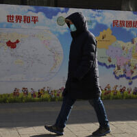 A man walks past a poster with the slogans 'World Peace' and 'Ethnic Unity' in Beijing, China, Jan. 11, 2021 (AP Photo/Ng Han Guan)