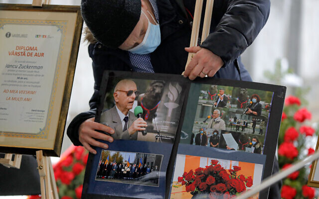 A man adjusts images of Iancu Tucarman, during his funeral, at a Jewish cemetery in Bucharest, Romania, January 11, 2021. (AP/ Vadim Ghirda)
