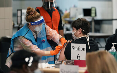 A health care worker administers a COVID-19 vaccination at the new Alamodome COVID-19 vaccine site, Jan. 11, 2021, in San Antonio, Texas (AP Photo/Eric Gay)