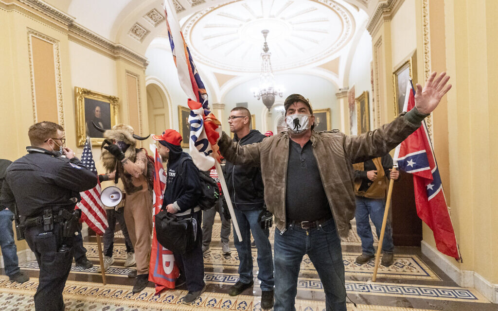 Insurrectionist supporters of US President Donald Trump are confronted by US Capitol Police officers outside the Senate Chamber inside the Capitol in Washington, January 6, 2021. (Manuel Balce Ceneta/AP)