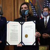 House Speaker Nancy Pelosi of Calif., displays the signed article of impeachment against US President Donald Trump in an engrossment ceremony before transmission to the Senate for trial on Capitol Hill, in Washington, Wednesday, Jan. 13, 2021. (AP Photo/Alex Brandon)