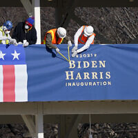 Workers put up bunting on a press riser for the upcoming inauguration of US President-Elect Joe Biden and Vice President-Elect Kamala Harris, on Pennsylvania Avenue in front of the White House, Thursday, Jan. 14, 2021, in Washington. (AP Photo/Gerald Herbert)