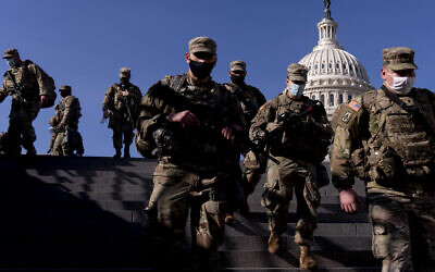 Members of the National Guard walk past the Dome of the Capitol Building on Capitol Hill in Washington Jan. 14, 2021. (AP/Andrew Harnik)