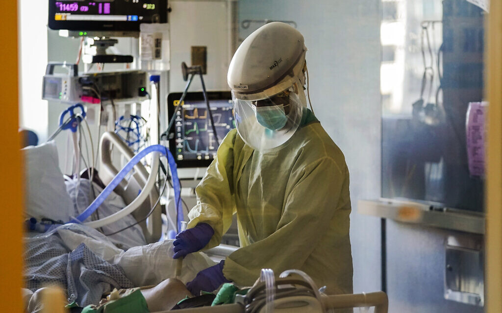 A healthcare worker tends to a COVID-19 patient in the intensive care unit at Santa Clara Valley Medical Center during the coronavirus pandemic in San Jose, California, January 13, 2021. (AP Photo/Jeff Chiu, File)