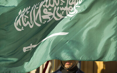 In this March 22, 2018, file photo, an honor guard member is covered by the flag of Saudi Arabia, in Washington (AP Photo/Cliff Owen, File)