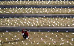 A man places flags at the National World War I Museum and Memorial Jan. 19, 2021, in Kansas City, Missouri. The 1,665 flags represent the area residents who died in the coronavirus pandemic and the display was part of a national memorial to lives lost to COVID-19. (AP Photo/Charlie Riedel)