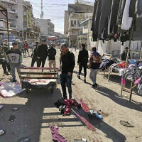 Civilians and security forces gather at the site of a deadly bomb attack in Baghdad's bustling commercial area, Iraq, January 21, 2021. (AP Photo/Hadi Mizban)