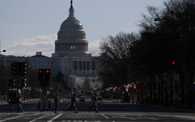 National Guard members jog across a road leading to the Capitol, after most downtown streets and public spaces had reopened to the public following the inauguration of President Joe Biden, on Saturday, Jan. 23, 2021 in Washington.(AP Photo/Rebecca Blackwell)