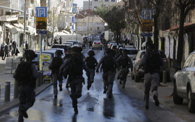Israeli police officers run in an ultra-Orthodox neighborhood, in Jerusalem, Jan. 24, 2021  (AP Photo/Sebastian Scheiner)