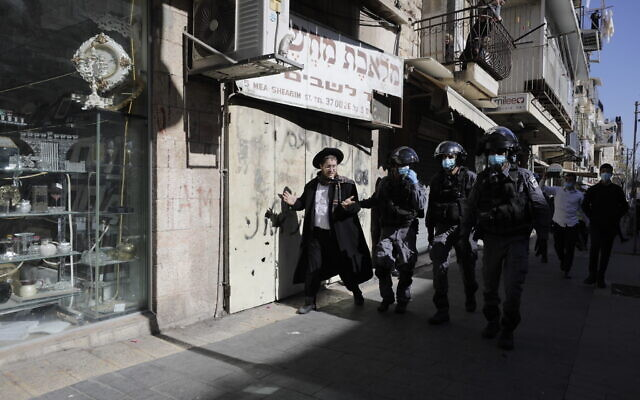 Israeli police officers detain an ultra-Orthodox man in Jerusalem, Jan. 24, 2021 (AP Photo/Sebastian Scheiner)