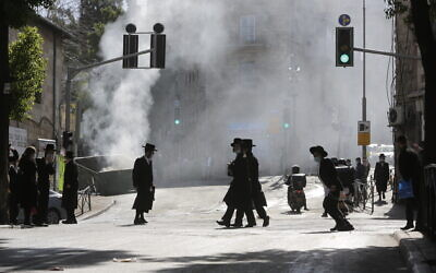 Men walk amid smoke from a dumpster fire, in an ultra-Orthodox neighborhood in Jerusalem, Jan. 24, 2021 (AP Photo/Sebastian Scheiner)